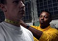 US Navy 060526-N-6463B-003 Chief Aviation Boatswain's Mate Handler James Hood checks neck measurement of Airman Apprentice Jered Yusten during Physical Fitness assessment (PFA) weigh-in.jpg