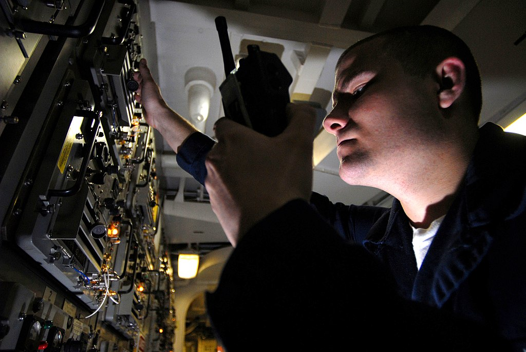 US Navy 070305-N-2659P-061 Electronics Technician Seaman Cliff Bunnowsky checks power inputs for Ultra High Frequency (UHF) radios used for ship-to-ship and shore communications in the Ultra High Frequency radio room