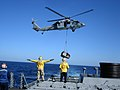 US Navy 071111-N-7400M-008 Seaman David Burley, a landing signal enlisted crewman aboard the guided-missile destroyer USS Russell (DDG 59), directs an MH-60S Seahawk helicopter carrying pallets of mail and food.jpg