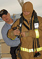 US Navy 071128-N-8544C-015 Precommissioning Unit (PCU) George H. W. Bush (CVN 77) Damage Controlman 1st Class Ken Alexander assists Executive Officer of the PCU Bush, Capt. Thom Burke don firefighting gear during basic damage c.jpg