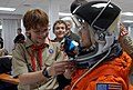 US Navy 081212-N-1825E-002 Caleb Vietinghoff adjusts the visor on a space suit helmet for a volunteer.jpg