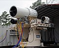 US Navy 100119-N-0365D-001 Members of the Directed Energy and Electric Weapon Systems Program Office fire a laser through a beam director on a Kineto Tracking Mount, controlled by a MK-15 Phalanx Close-In Weapons System.jpg