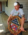 US Navy 100505-N-5862D-003 Navy housing resident Larry Stivers salvages his retirement shadow box after being allowed back to his home in the base housing area of Naval Support Activity Mid-South.jpg