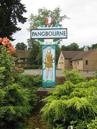 Pangbourne - Village name sign by its secular parish hall with homes in background.