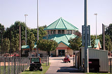 A hexagonal building with a green roof is partly surrounded by trees, fences, and lights on tall poles. A man in a baseball-style cap is driving a small machine across a paved surface near the hexagonal building. Another machine with the letters T-O-R-O on its rear bumper is parked on the grass nearby.
