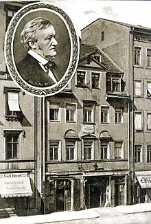 A postcard of a five-storey building with shops on the ground floor and garret windows in the roof. A round inset has a picture of Wagner in middle age.