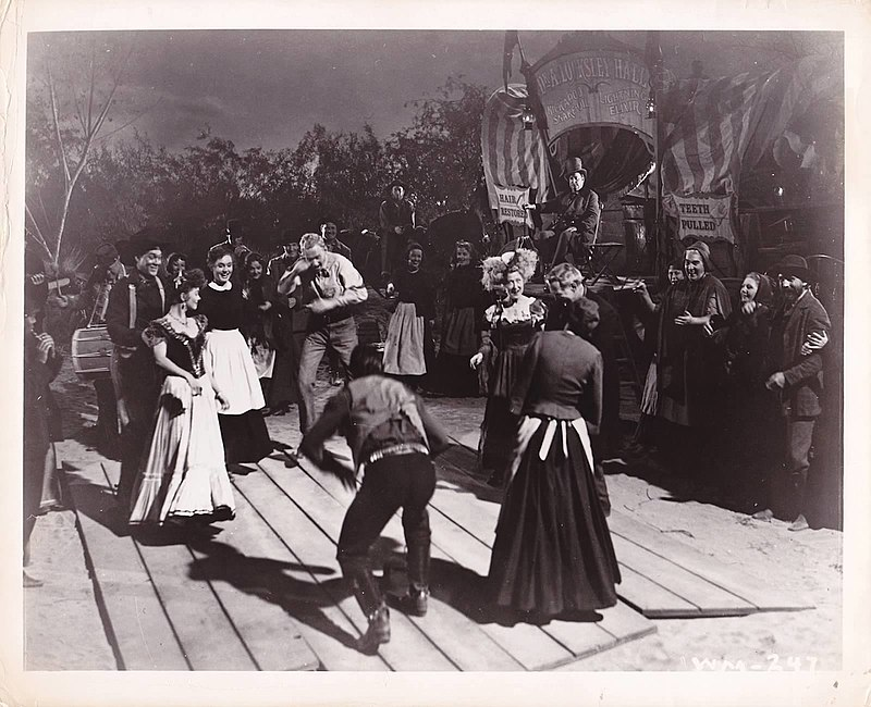 "This is an outdoor scene with trees and the night sky visible in the background. In the foreground is a wooden dance floor consisting of long wooden boards butted roughly together. Four couples form the four sides of a square about 10 feet across. Two of the men are starting to move towards the center; all of the individuals are smiling and jovial. In the background there are about twenty more people watching, and behind them on the right there is a medicine show wagon. The wagon has several signs and banners. The topmost and largest reads ""Dr. A. Locksley Hall""; smaller signs say ""Hair Restored"" and ""Teeth Pulled"". A man in a top hat is sitting regally on a small platform in front of the wagon. On the left are two musicians, one playing a flute and the other carrying a drum."