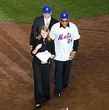 Mays în uniformă New York Mets stă pe un teren de baseball și zâmbește, însoțit de un bărbat într-un costum cu o șapcă de baseball New York Mets și o femeie într-o rochie neagră cu un microfon care vorbește