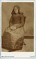 Äldre kvinna poserar i en dräkt med huvudbonad till - Nordiska Museet - NMA.0060794.jpg