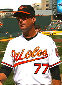 "A man wearing a white baseball jersey with ""Orioles"" in orange script across the chest and the block number ""77"" in orange below it; he is also wearing a black baseball cap with an orange and black bird on the front and an orange brim"
