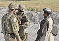 A linguist assists U.S. Army Pfc. John T. Roquemore, center, with the 2nd Battalion, 23rd Infantry Regiment, in conducting biometric enrollments during a traffic checkpoint in the Panjwai district, Kandahar 130516-A-MX357-038.jpg