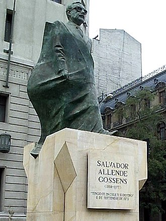 Salvador Allende - Statue of Allende in front of the Palacio de la Moneda. A portion of the statue's drapery, shown worn as a cape, is the national flag of Chile.