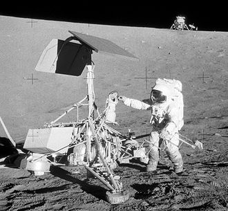 Surveyor program - Astronaut Pete Conrad jiggles the Surveyor 3 craft. Human scale demonstrates typical lander height of 3 meters. Lunar module is about 200 meters away, in the background. (NASA)