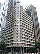 Beige rectangular building, 20 storeys and at 87 metres tall, with newer taller skyscrapers seen in the background.
