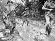 A black and white photograph of Australian soldiers patrolling along a muddy track surrounded by thick jungle. The men are armed with rifles which are held at the high port position and are wearing tropical uniforms consisting of shorts and lightweight short sleeve shirts. One of the soldiers is patrolling without a shirt.