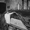 Bij de grafsteen tilt de vermoedelijke bewakergastheer het fluwelen doek op om , Bestanddeelnr 255-2333.jpg