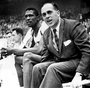 Red Auerbach - Bill Russell (left) sitting on the bench next to Auerbach during a game at Boston Garden on December 26, 1956. Bob Cousy can be seen in the background.