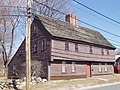 A brown garrison-style saltbox house with a wooden roof and a red door. A rough stone wall separates the street from the yard.