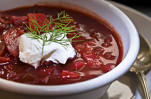 A bowl of borscht garnished with dill and a dollop of smetana (sour cream)