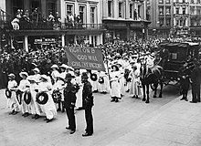 "A procession of Suffragettes, dressed in white and bearing wreaths and a banner reading ""Fight on and God will give the victory"" during the funeral procession of Emily Davison in Morpeth, Northumberland, 13 June 1913. Crowds line the street to watch."