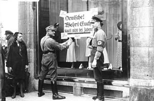 "1933 in Germany - 1 April: Nazi soldiers hang a poster on the window of Jewish-owned business, that says: ""German, protect yourself. Do not buy from Jews""."
