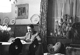 Photo noir et blanc montrant Adolf Hitler, assis à une table, dans une pièce de sa résidence secondaire du Berghof (à Berchstesgaden). L'homme, en costume clair, de face, est en train de lire des documents. L'arrière-plan est divisé par un rideau aux motifs fleuris: à droite, une fenêtre fermée au bord chargé de pots de plantes et, à gauche, un mur blanc supportant un tableau et un meuble en bois d'une couleur foncée sur lequel sont posées, sur la tranche, trois assiettes.