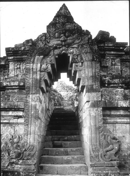 "File:COLLECTIE TROPENMUSEUM De toegangspoort van de noordelijke<br /><br>ingang tot het tempelcomplex van de Borobudur TMnr 60009721.jpg"" width=""420″ height=""599″ /></a></p><br><p>Borobudur gate with Kala at the top ""devouring"" the worshipper as they climb through the galleries to reach the stupa at the top.  The galleries at the bottom depict everyday life from the <em>Jataka</em> tales, and as one moves higher we see reliefs of the journey to become a <em>boddhisattva</em>.  The topmost terraces contain Buddhas, and thus, the mandala represents a movement in time toward ultimate enlightenment and Nirvana, which is possibly symbolized by the empty stupa at the apex. The Kalacakra Deity is the pantheistic source (Adibuddha) — the Fractal Self — in Kalacakra Buddhism and is seen as a personification of time, a belief that also is found in indigenous systems of Southeast Asia. (Source:<a href="