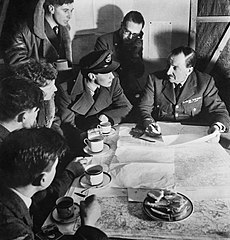 Cecil Beaton photograph of an RAF bomber crew being debriefed by the squadron intellgence officer on their return from a night raid over Germany, 1941. D4750.jpg