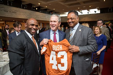 (L-R) Charlie Strong, Texas Longhorns head football coach, George W. Bush and Reverend Jesse Jackson hold up a Texas Longhorns football jersey at the LBJ Presidential Library in 2014 Charlie Strong with George W. Bush and Jesse Jackson.jpg