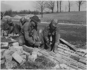 Five workmen. One is holding a shovel, while the other four are laying bricks to form a drainage ditch along the side of a road.