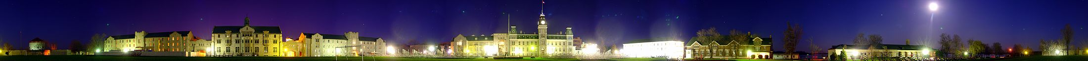 A 260-degree photo of the Royal Military College of Canada in Kingston, Ontario, on 4 May 2007. Seen is a green landscape during the night, featuring buildings made of white stone and red brick. The night sky is dark blue and purple, with the moon shining bright on the right side of the image. Photo credit: Martin St-Amant (User:S23678)