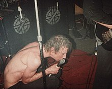 Shirtless male singer crouching onstage