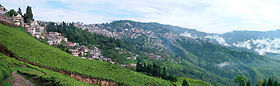 A panoramic view of a hill range. The upper portions of the nearer hillsides have tiled houses, while the farther hillsides and the lower portions of the nearer ones are covered with green bushes. A few coniferous trees are scattered throughout.