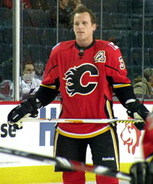 "A Calgary Flames player observes his teammates who are off camera.  On his uniform is a small patch that uses Atlanta's ""Flaming A"" logo to denote his position as an alternate captain."