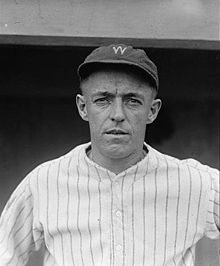 "A man wearing a pinstriped baseball jersey and a cap with the letter ""W"" written on the front."