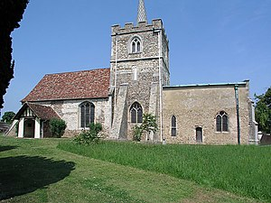 A stone church seen from the south, with a central battlemented tower, the nave with a porch and red tiled roof to the left, and a smaller chancel with a flat copper roof to the right
