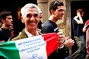 Smiling older man in a parade, holding a decorated Italian flag