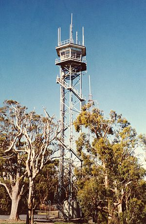 A tall metal tower with a very small enclosed cabin at the top.
