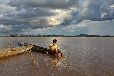 Fishing boy sitting on a boat in Laos