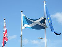 The Scottish, UK and EU flags flying outside the Parliament.