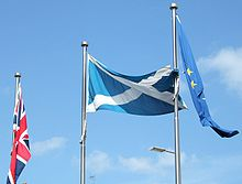 Union Flag, Scottish Flag and European Flag on poles against a blue sky.
