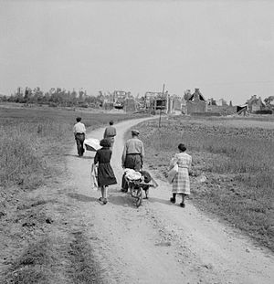 Buron - A French family return to their village, Buron, on July 18, 1944; it was devastated during the Battle of Normandy.