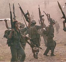 Several Nicaraguan Contras brandishing assault rifles and RPGs.
