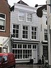 foto van Huis met gepleisterde ingezwenkte lijstgevel. In lijst gedateerd. Winkelpui