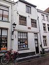 foto van Huis met gepleisterde lijstgevel, uitgekraagde puilijst, ramen met kleine roedenverdeling, schilddak. Lelie-ankers