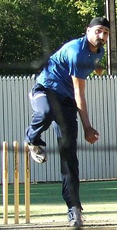 Man with black beard in a black turban, wearing navy tracksuit pants, blue T-shirt, follows through after bowling a ball in the cricket nets. His left leg is perpendicular to the ground, and his right leg is raised and bent back at the knee. His right bowling arm has rotated down to his side after releasing the ball.