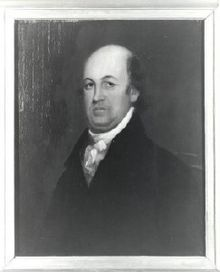 A balding man wearing a black jacket and white shirt