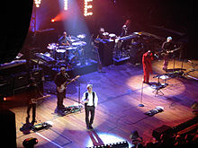 "David Bowie on stage in 2002; a portion of the lights' ""W"",""I"" and ""E"" are visible at the top of the picture"