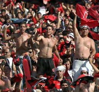 Barra brava - Supporters of Newell's Old Boys (club from Rosario, Argentina) standing upon a metal crush barrier.