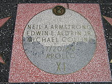 Moon Landing monument, with square pink terrazzo surround (not the usual charcoal color), with light gray terrazzo Moon disk showing TV emblem at top and the brass lettering
